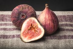 Macro view of fresh brown figs on striped linen towel. stock photo