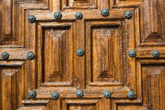 A close-up view to a part of old brown wooden door. With metal rivets Stock Image