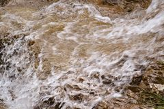 Close-up view to pure water flowing on rocks in mountains. stock image