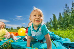 Close-up view of toddlers sitting on blanket. In the field during sunny summer day Royalty Free Stock Photos