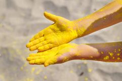Closeup top view of empty cute child`s hands dirty because of colorful powder. yellow paint Holi on the beach. royalty free stock images