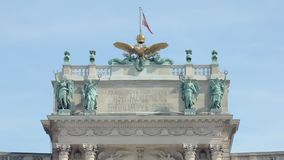 Close-up view of top of old austrian government building with decoration. And swaying flag stock footage