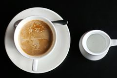 A close-up view of the top and side cups of coffee and a saucer and a jug with milk. A close-up view of the top and side cups of coffee and a saucer and a jug stock photos