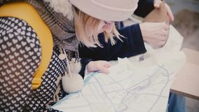 Close-up view of tourist man and woman looking close at a city map travel guide sitting outside together on a winter day. Happy young friends spend fun time stock video