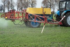 Close-up view of the tractor spraying the chemicals on the large. The close-up view of the tractor spraying the chemicals on the large green field Royalty Free Stock Image