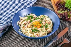 Close up view on traditional homemade carbonara in blue bowl served on table. royalty free stock photo