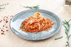 Close up view on traditional italian pasta with cherry tomato, herbs and spices on wooden background. stock image