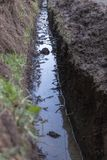 A Trench. A Close up view of a trench that has been dug next to a drive way to put in water pipes stock photo