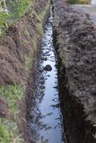 A Trench. A Close up view of a trench that has been dug next to a drive way to put in water pipes stock photography
