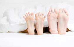 Close up view of feet of the couple lying in bed Royalty Free Stock Image