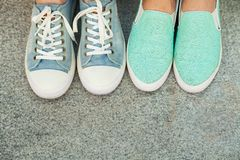 Two pairs of teen`s feet in sneakers Royalty Free Stock Photos