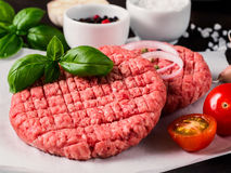 Close up view of two raw meat steak cutlets for burger with vegetables. Spices and fresh basil. Making homemade burger Stock Photography