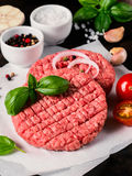 Close up view of two raw meat steak cutlets for burger with vegetables. Spices and fresh basil. Making homemade burger. Vertical Stock Images