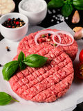 Close up view of two raw meat steak cutlets for burger with vegetables. Spices and fresh basil. Making homemade burger. Vertical Royalty Free Stock Image