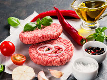 Close up view of two raw meat steak cutlets for burger with vegetables Stock Photos