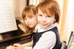 Close-up view of two small girls playing piano Royalty Free Stock Photo