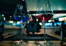 Close up view of two wineglasses poured by wine of different colors. Close up view of two glasses of wine poured by wine of different colors - red and blue royalty free stock photo