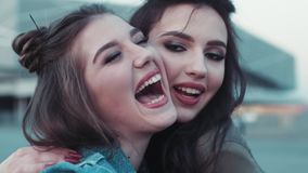 Close up view of two young girls with beautiful makeup going crazy, laughing, hugging. Natural beauty, jeans wear