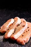 Close up view on uncooked meat seasoned with spices, pepper and Royalty Free Stock Image