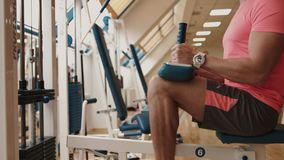 Close-up view at the unknown athletic muscular sportsman training his legs at the curls trainer in the fitness club. 4k. Footage stock video footage