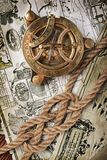 Close-up view of a vintage compass and a knot of rope on an old retro map Royalty Free Stock Photography