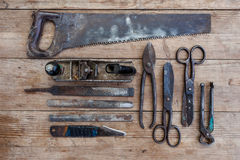 Close up view vintage rusted tools on old wooden table: pliers, pipe wrench, screwdriver, hammer, metal shears, saws and other Royalty Free Stock Photos