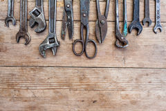 Close up view vintage rusted tools on old wooden table: pliers, pipe wrench, screwdriver, hammer, metal shears, saws and other. Royalty Free Stock Images