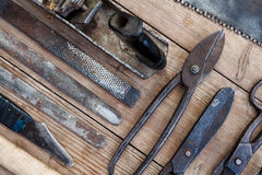 Close up view vintage rusted tools on old wooden table: pliers, pipe wrench, screwdriver, hammer, metal shears, saws and other. Stock Image