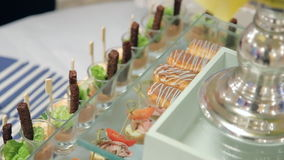 Close-up view of waiter putting eclairs on glass stand on table. stock video footage