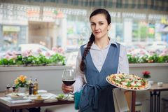 Close up view of waiter serving dishes at restaurant. Background Royalty Free Stock Photos