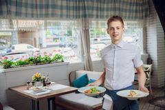 Close up view of waiter serving dishes at restaurant royalty free stock photos