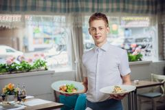 Close up view of waiter serving dishes at restaurant. Background Royalty Free Stock Images