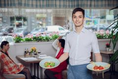 Close up view of waiter serving dishes at restaurant. Background Royalty Free Stock Photography