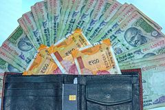 Close up view of wallet with 200 rupees and old 100 rupees Indian banknotes on background royalty free stock photography