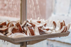 A close-up view of water drops falling on coconut slices at local market for sale. Royalty Free Stock Photography