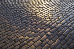 Close up view of wet, dark and sunlit cobble paved street, Edinburgh royalty free stock images