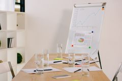 Close up view of white board with graphic, papers and glasses of water on table. In office stock image