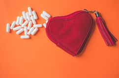 Close up view of white capsules spilling from a heart shaped wallet on orange background royalty free stock photography