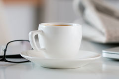 Close up view of white coffee cup on table with glasses and news Royalty Free Stock Photos