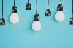 Close up view of white lamps pretending hanging on lamp holders. On blue Stock Photos