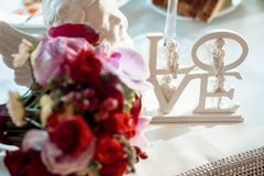 Close-up view of the white letters ``love`` decorated with angels placed on the table near blurred bouquet of colourful stock photos