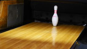 Close-up view of white pins standing in th end of bowling alley lane and rolling bowling ball in a sport club. Media stock video