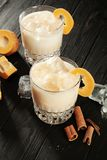 Close up view on white proteinaceous egg cocktail in glasses. Glass with ice, pumpkin and cinnamon standing on dark background stock images