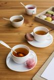 Close-up view of white tea cups and tasty macarons. On table stock photography