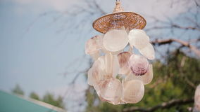 Close-up view of wind chime on a tree. Bright sunny day, decoration for backyard outside. Close-up view of wind chime for the porch on a green tree. Bright stock footage