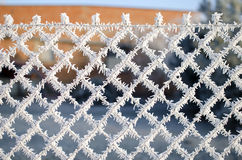 Close-up view of a wire fence with frost with ice crystals under a blue sky with a blurred background Royalty Free Stock Photo