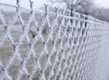 Close-up view of a wire fence with frost with ice crystals under a blue sky with a blurred background Stock Image