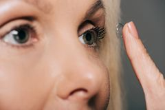 close-up view of woman applying contact lens stock images