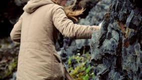 Close-up view of woman climbing in the mountains near the river. Traveling female hiking in the rocks alone. Tourist girl exploring the new beautiful place stock footage