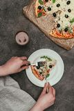 Close-up view of woman cutting a slice of pizza royalty free stock image